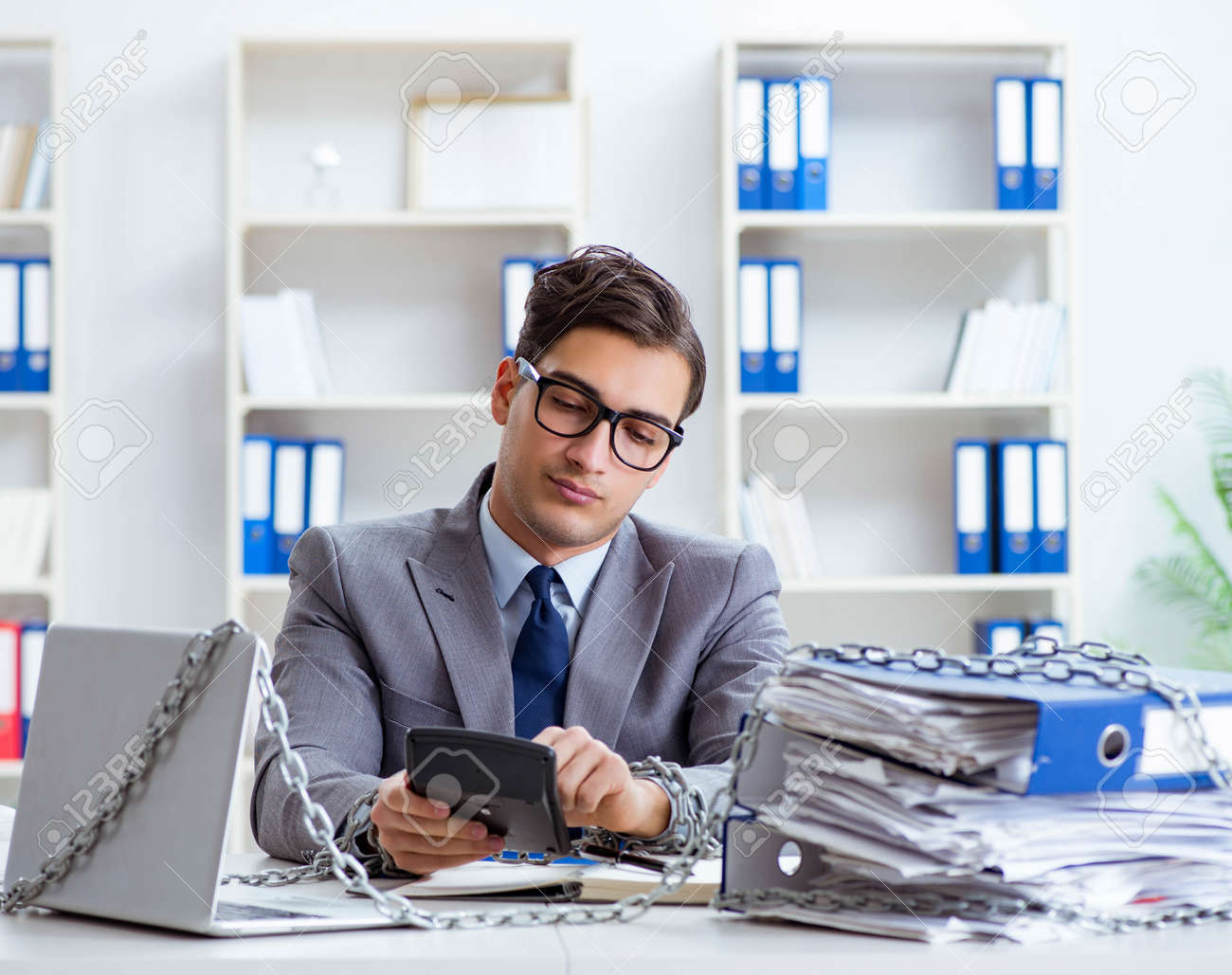 Busy employee chained to his office desk - 153212972