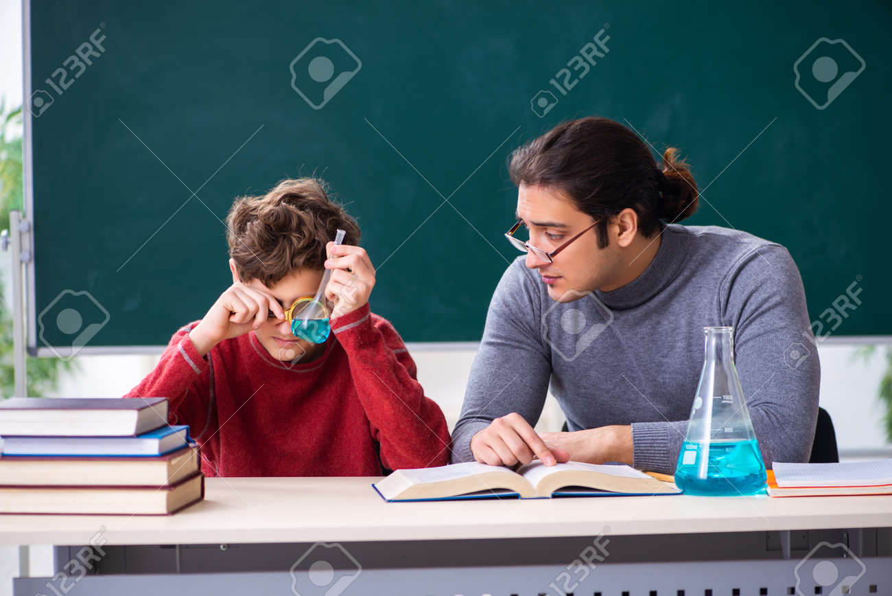 Young male teacher and schoolboy in the classroom - 154351889