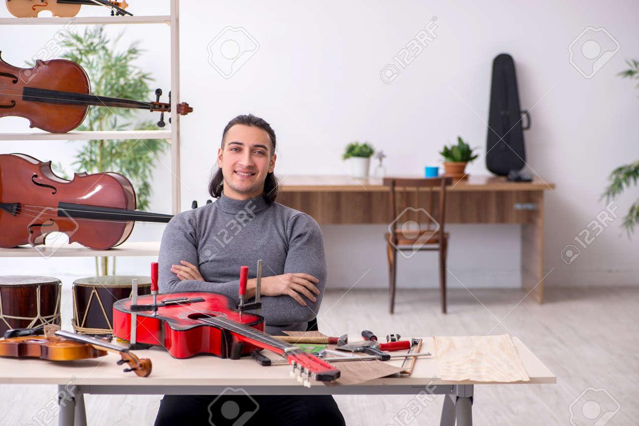 Young male repairman repairing guitar - 154378079