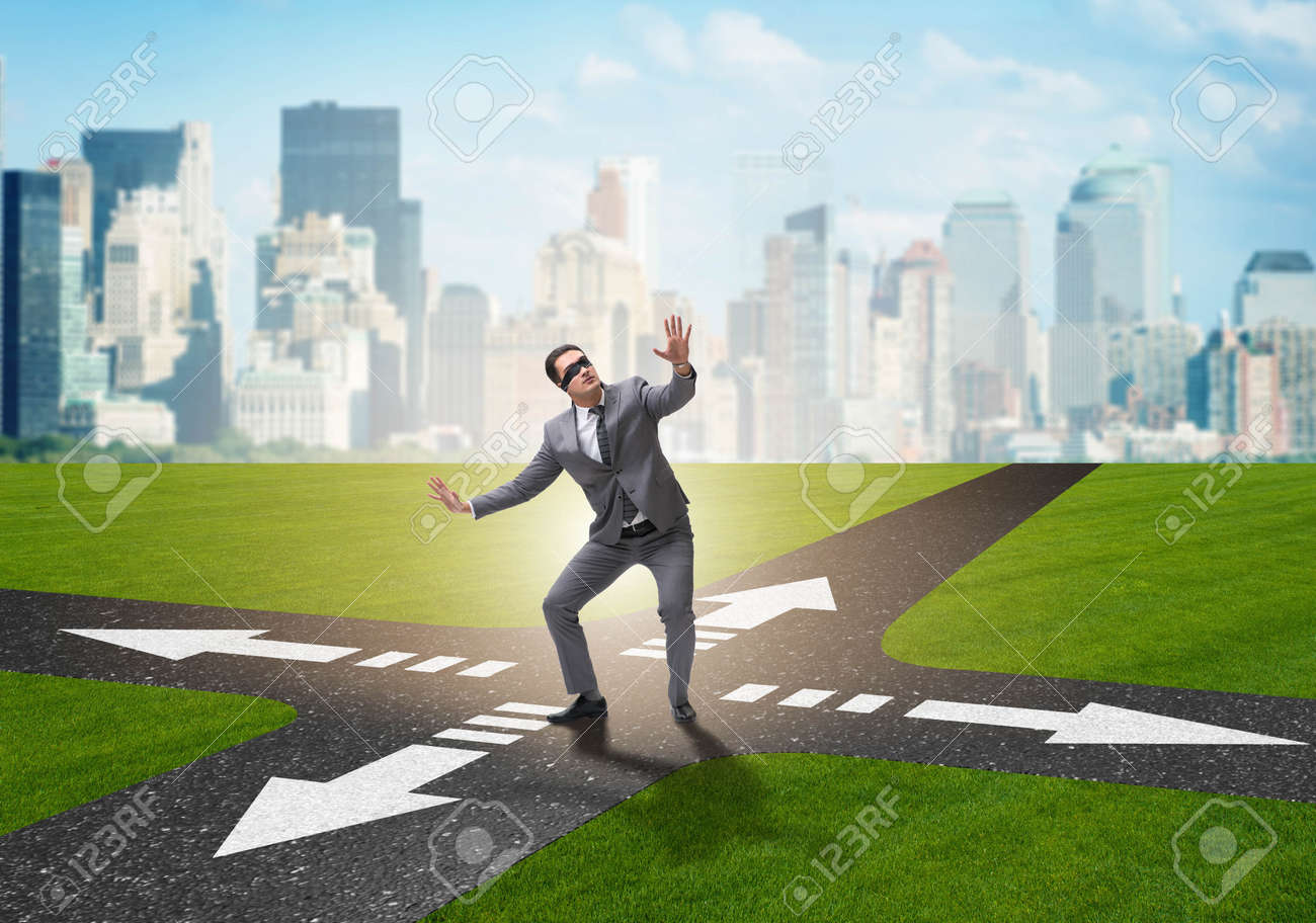 Young businessman at crossroads in uncertainty concept - 156584351