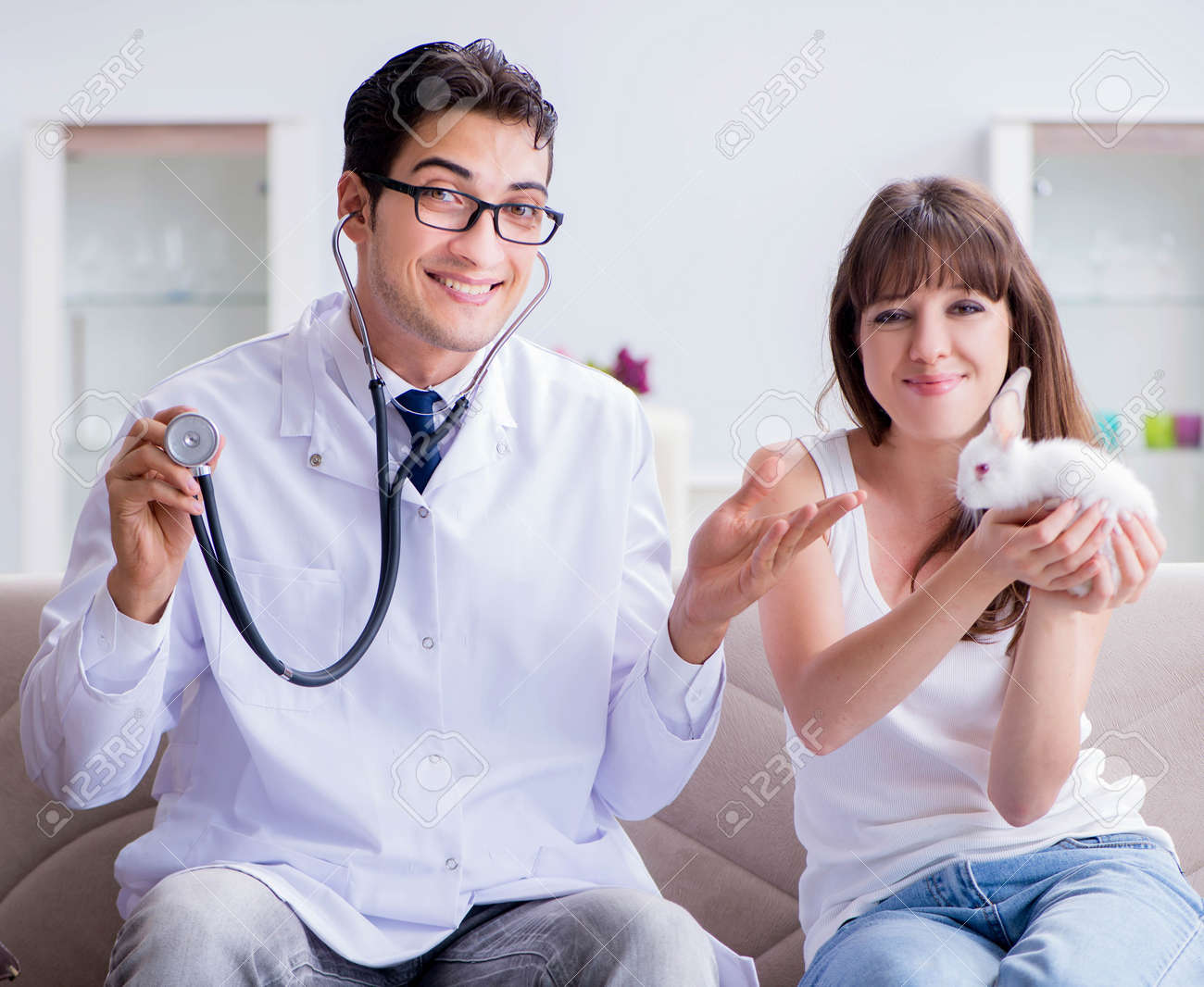 Woman with pet rabbit visiting vet doctor - 157413653