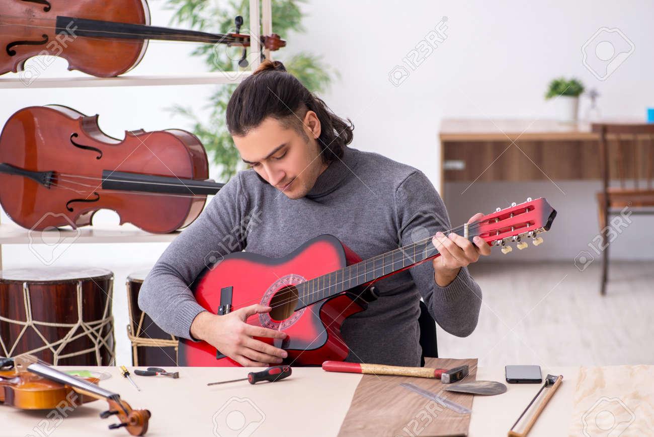 Young male repairman repairing guitar - 157707196