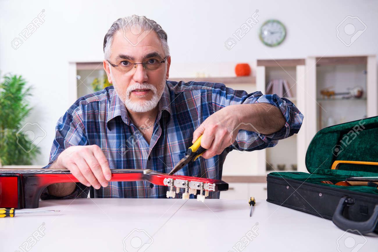 Senior male repairman repairing musical instruments at home - 157747067