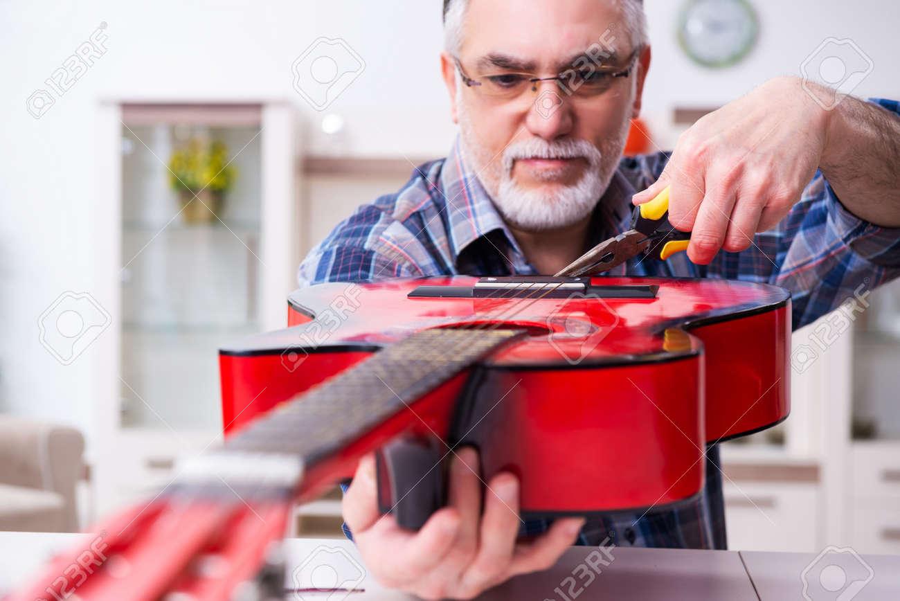 Senior male repairman repairing musical instruments at home - 159333655