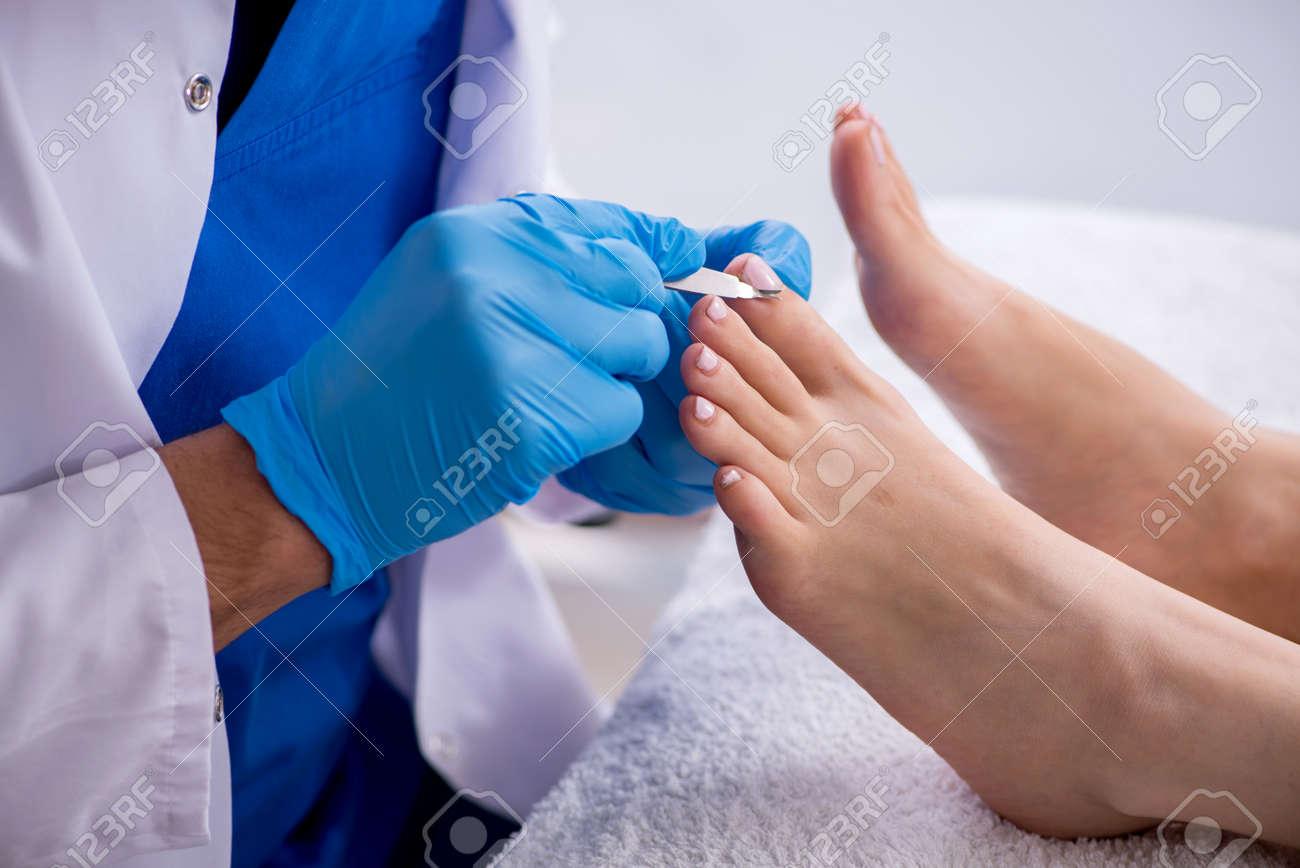 Podiatrist treating feet during procedure - 159452212