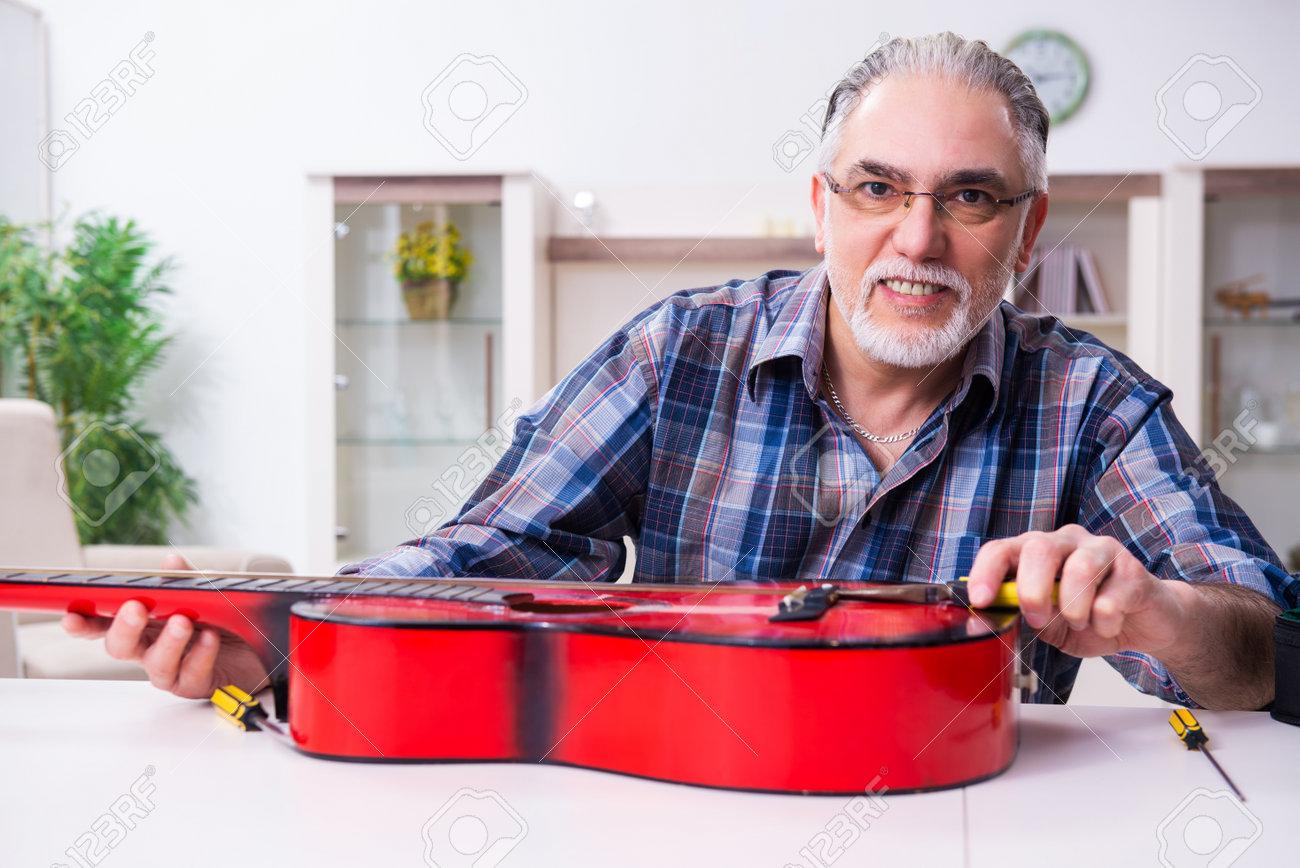Senior male repairman repairing musical instruments at home - 160281537