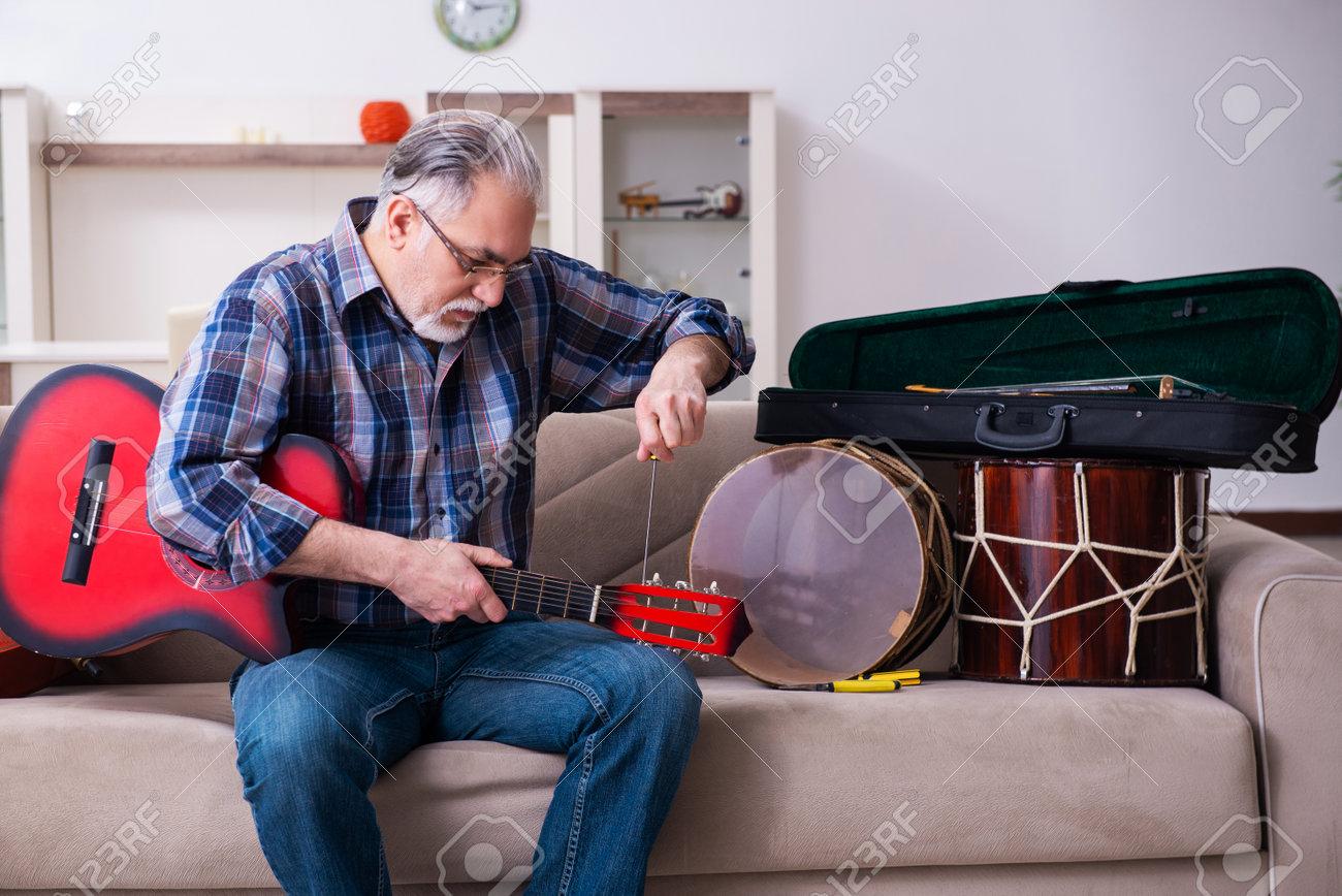 Senior male repairman repairing musical instruments at home - 162961121