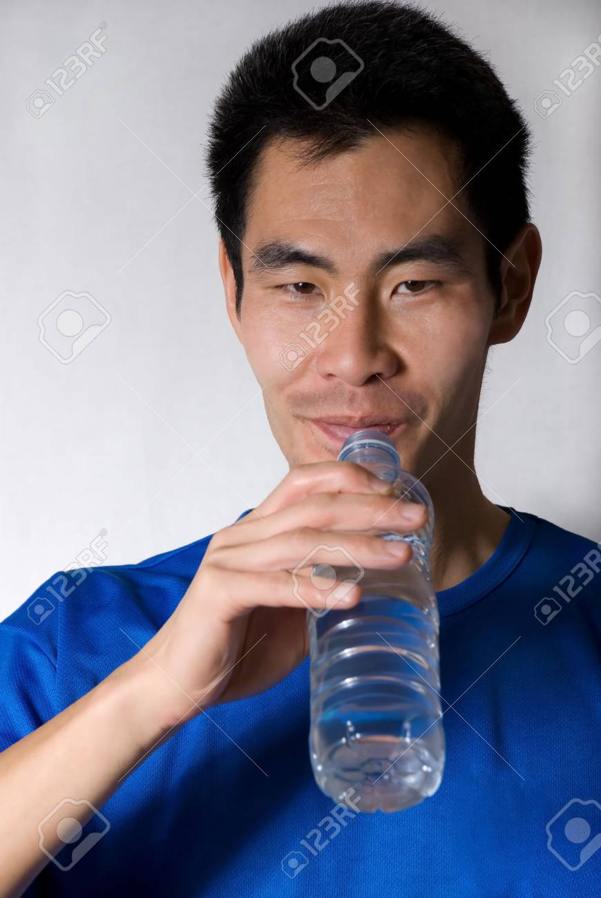 asian man drinks water out of a small water bottle Stock Photo - 16239276