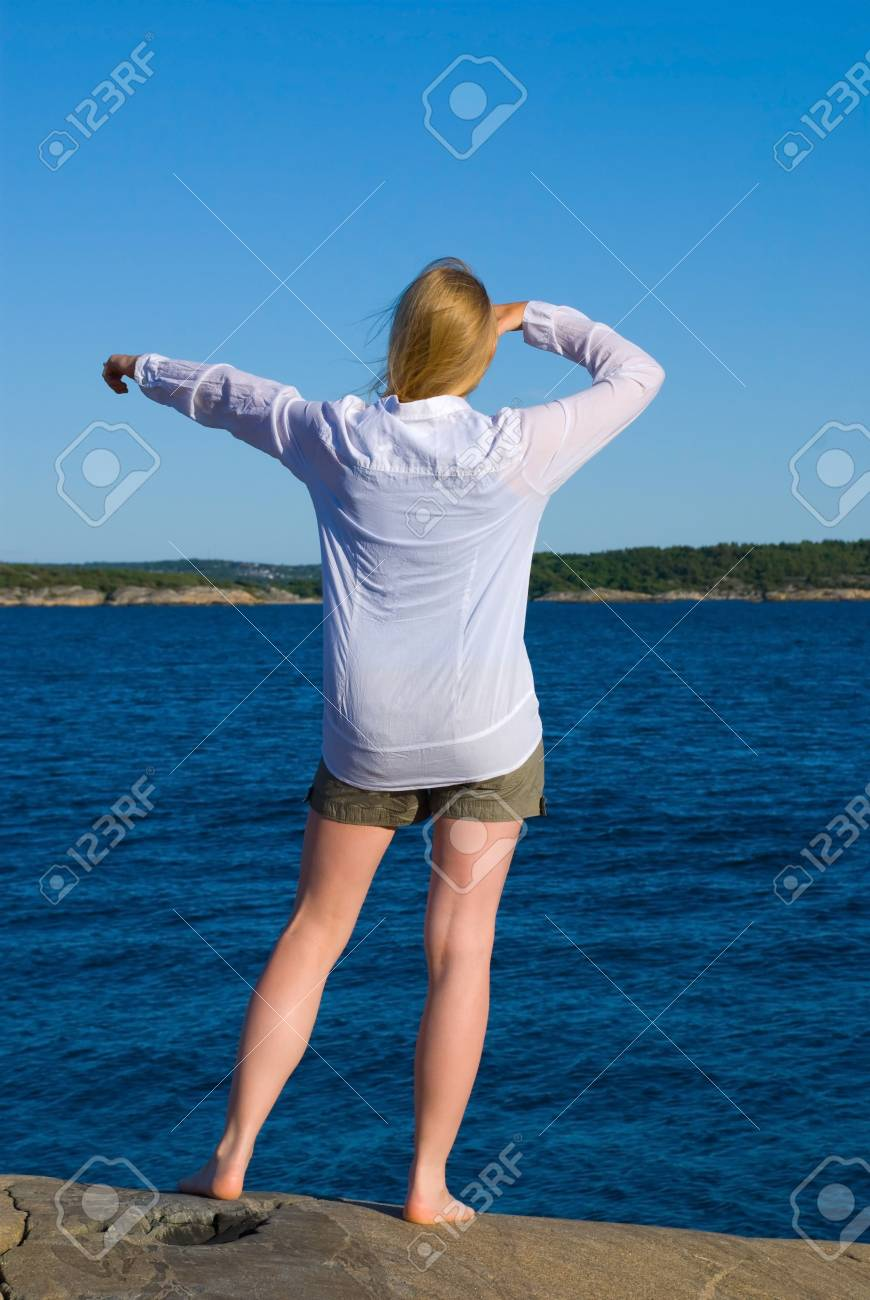 a woman stands at the coast and shows something in front of the ocean Stock Photo - 16327324