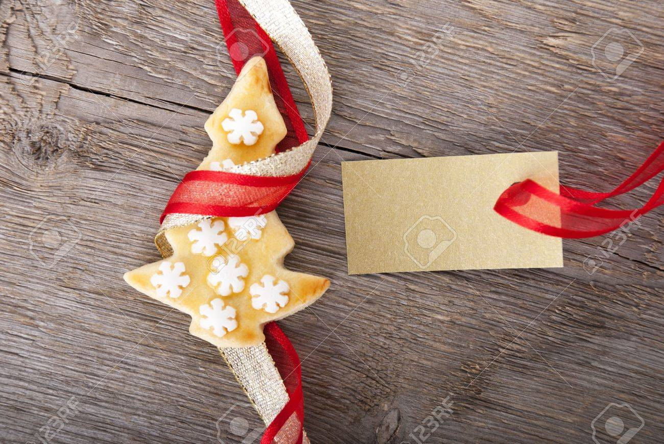 a golden tag with copy space and a christmas cookie as christmas background Stock Photo - 21577102