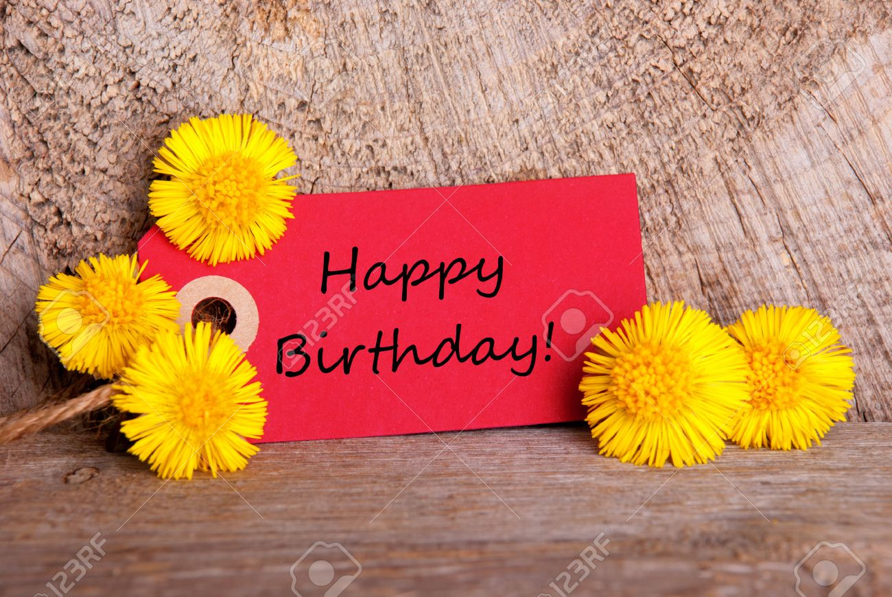 Red Tag With Happy Birthday On It And Yellow Flowers Stock Photo