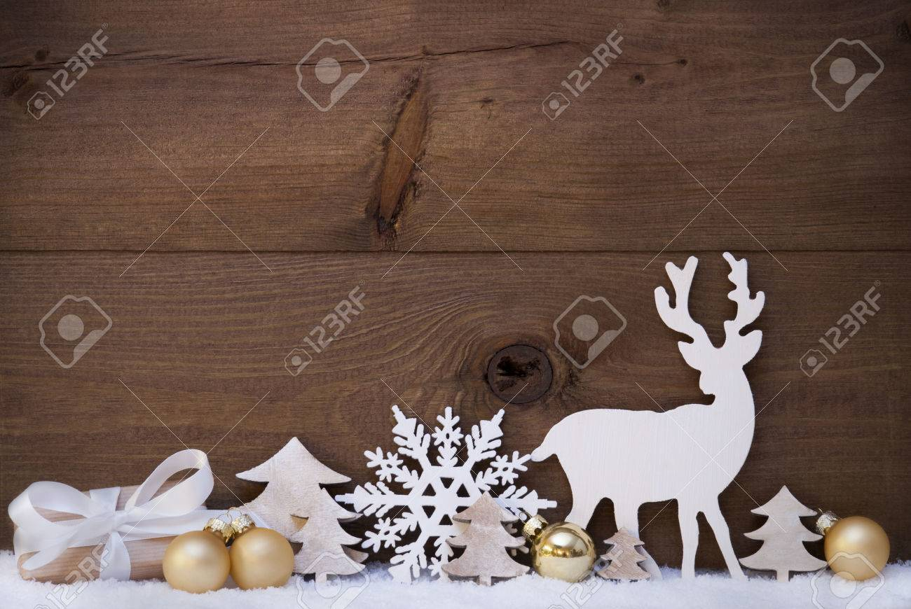 christmas card with golden festive decoration on snow gift present white reindeer