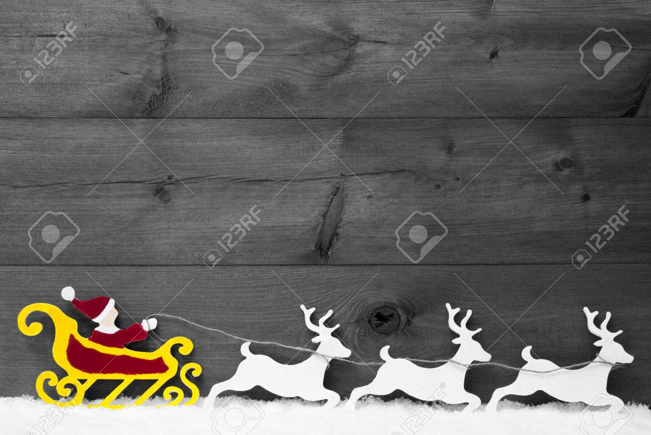 Christmas decoration red santa claus with yellow sled and white reindeer on snow brown