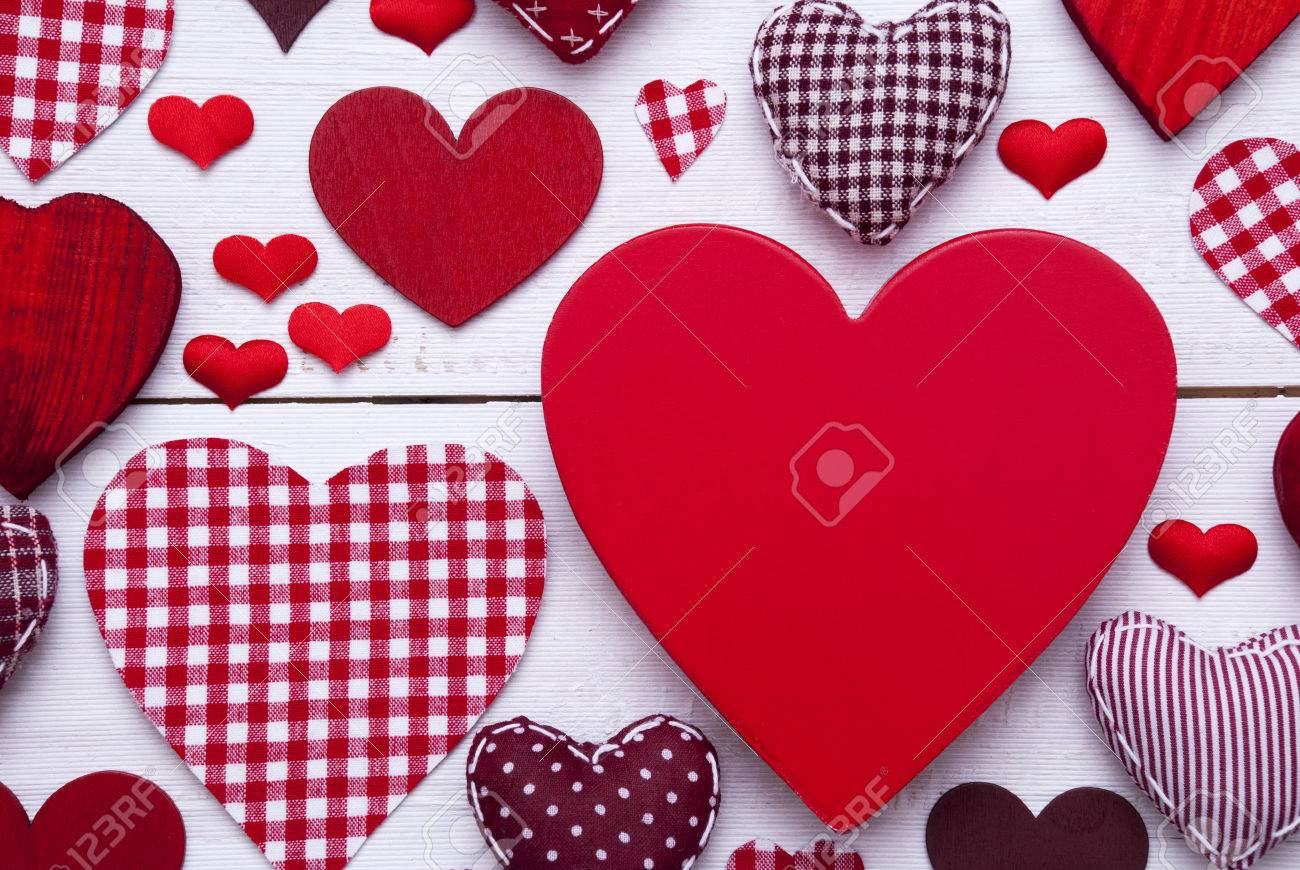 texture with many red fabric hearts on white wooden background romantic decoration for valentines day