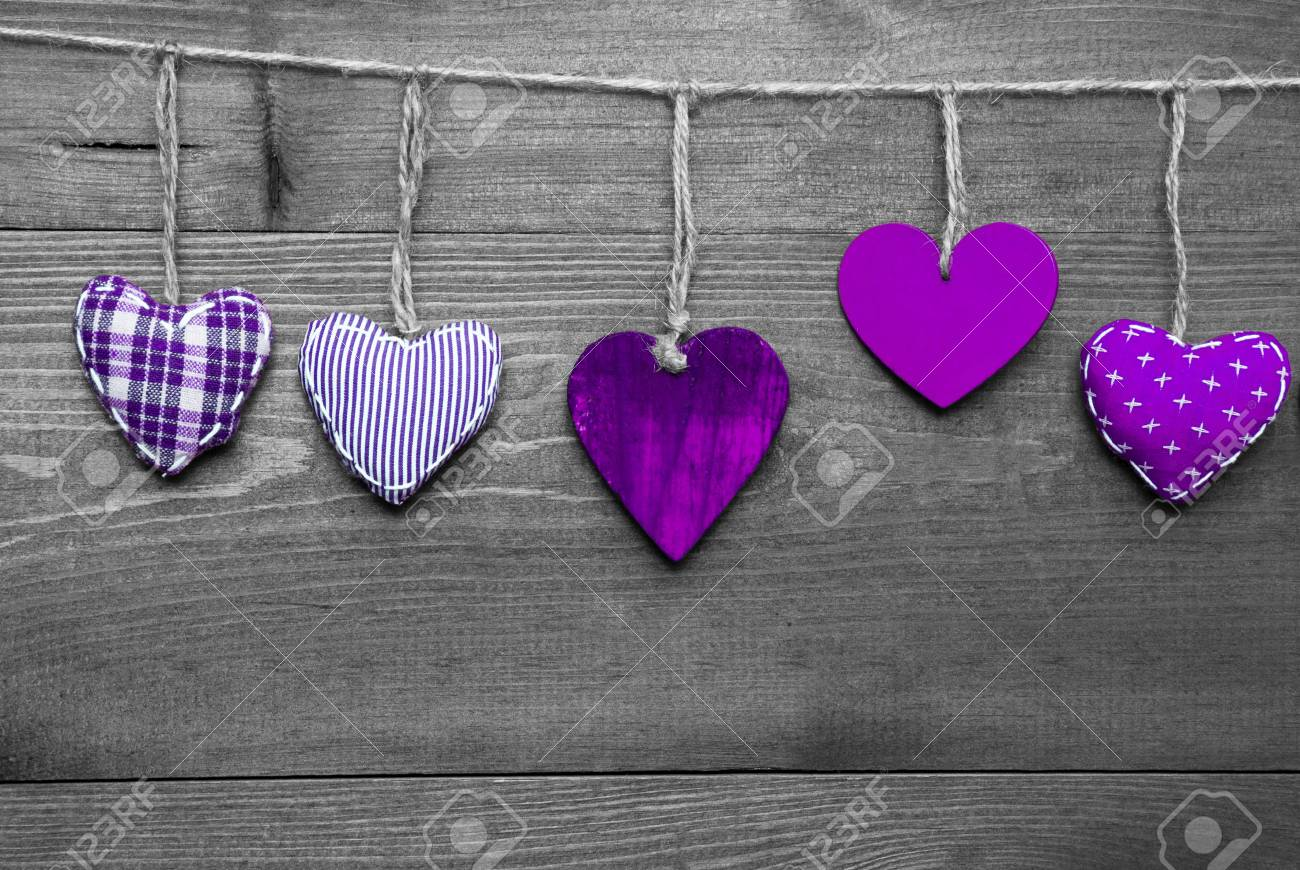 57427147 wooden background with purple hearts hanging in a row black and white style with colored hot spots c jpg