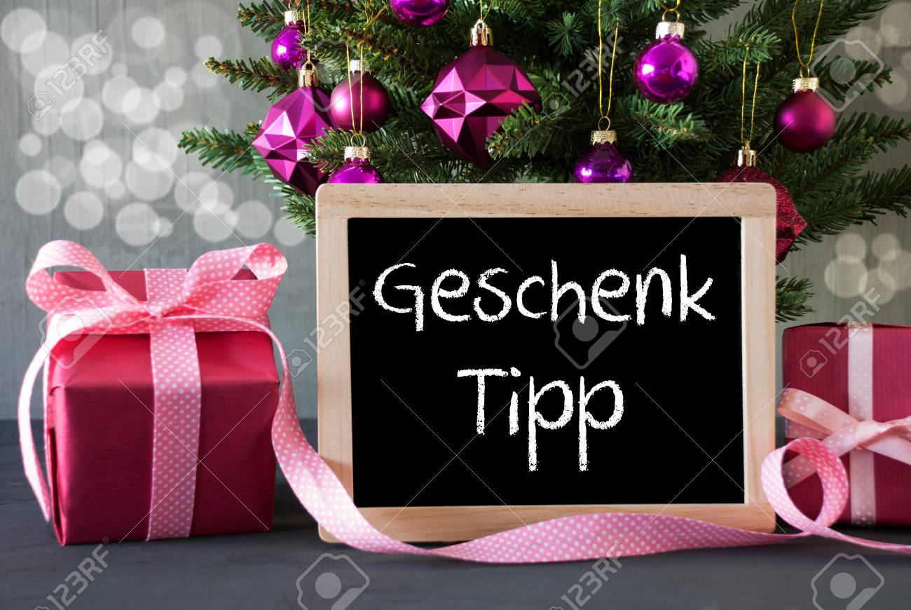 chalkboard with german text geschenk tipp means gift tip christmas tree with rose quartz balls