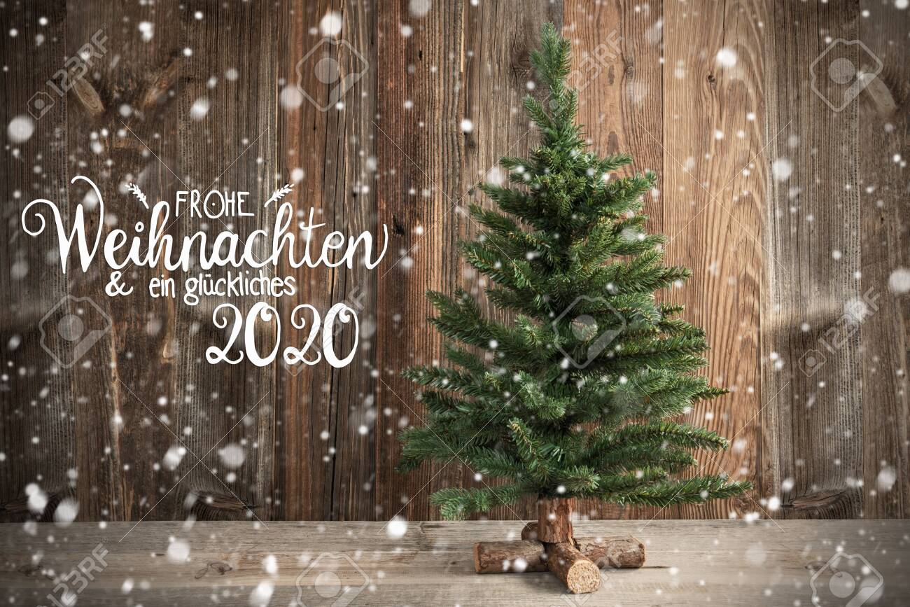 German Calligraphy Frohe Weihnachten Und Ein Glueckliches 2020 Means Merry Christmas And Happy New Year 2020. Christmas Tree Infront Of Brown Rustic Wooden Background With Snow - 133973649