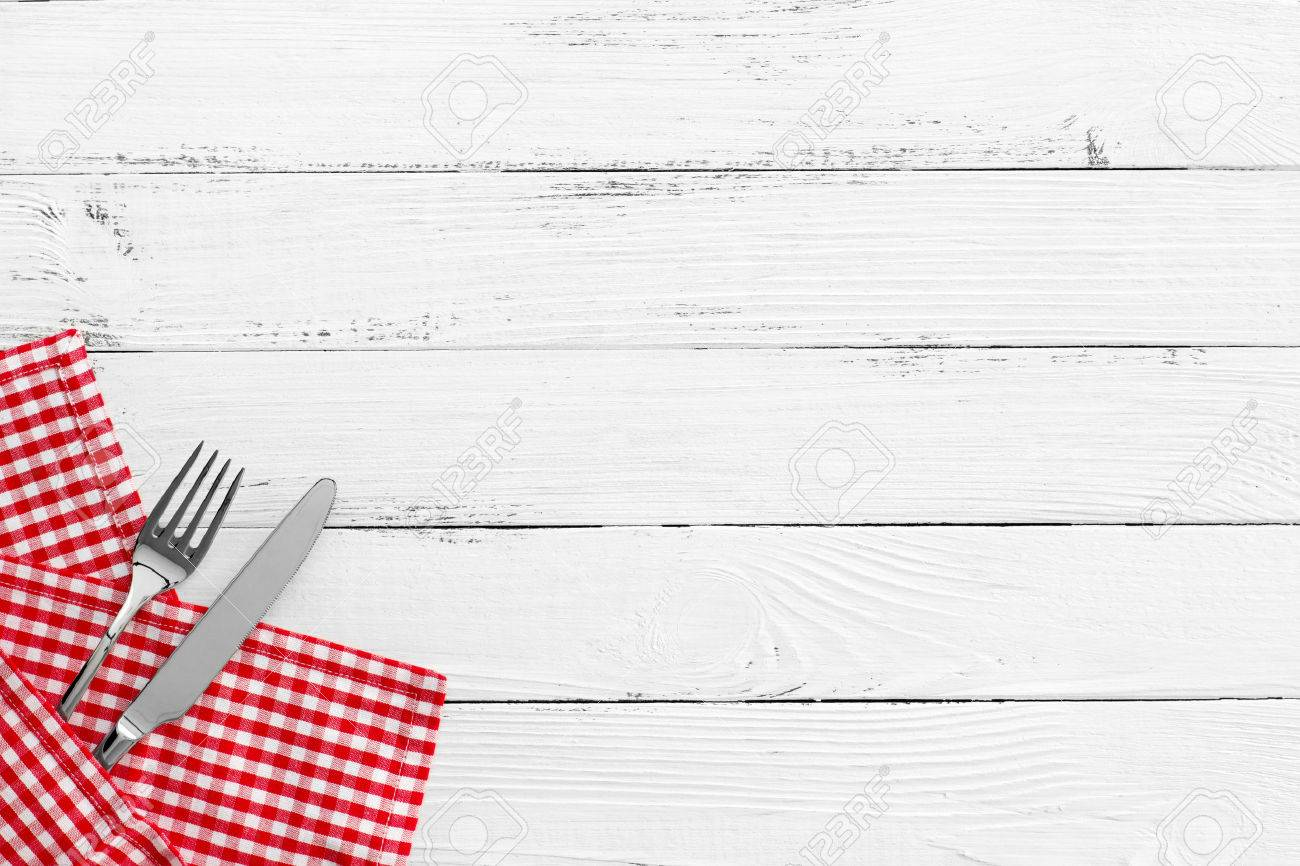 Knife And Fork On White Old Vintage Wooden Table With Red Checked Tablecloth  And Copyspace.
