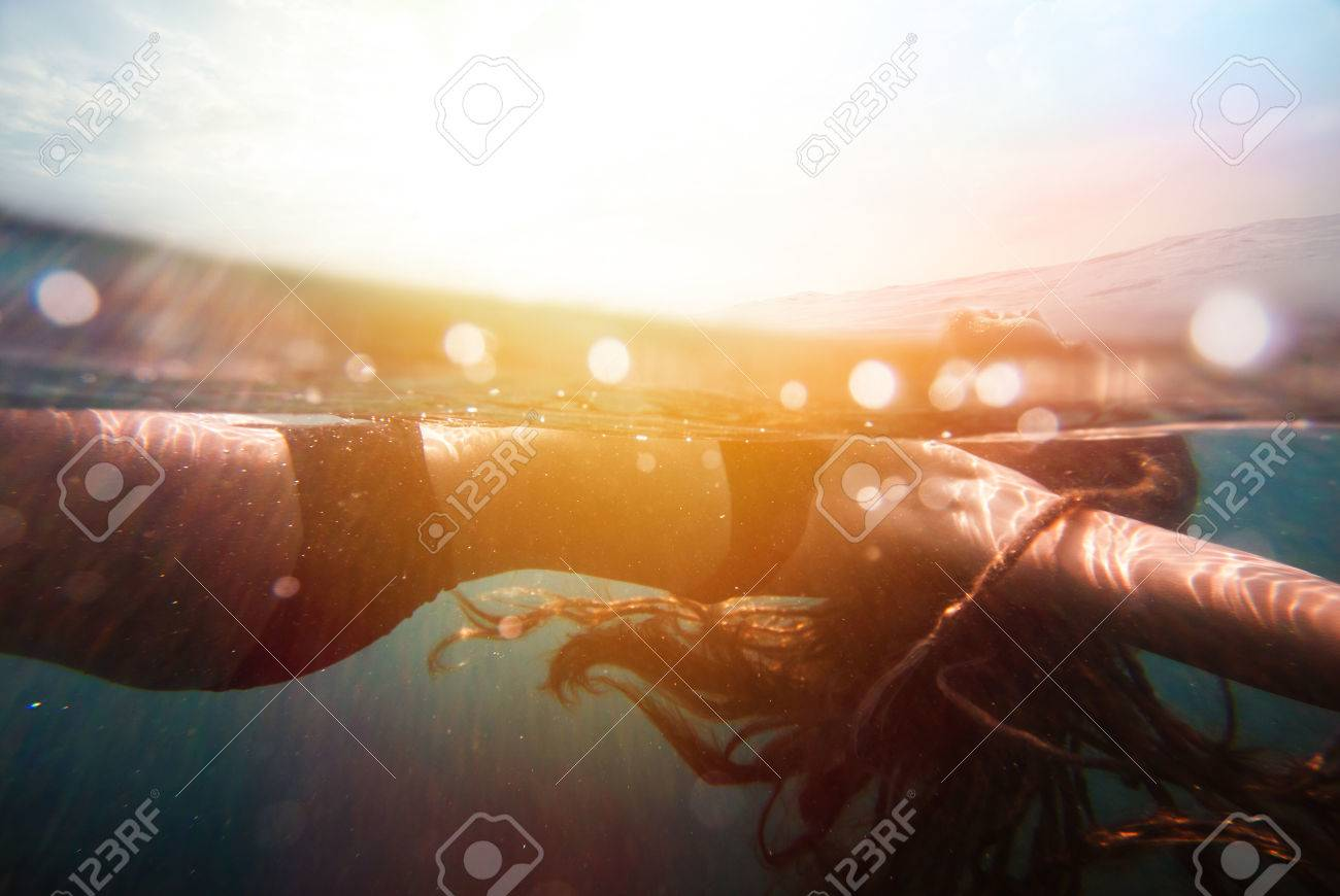 Girl underwater with sun rays and colorful sunflare - 34786193