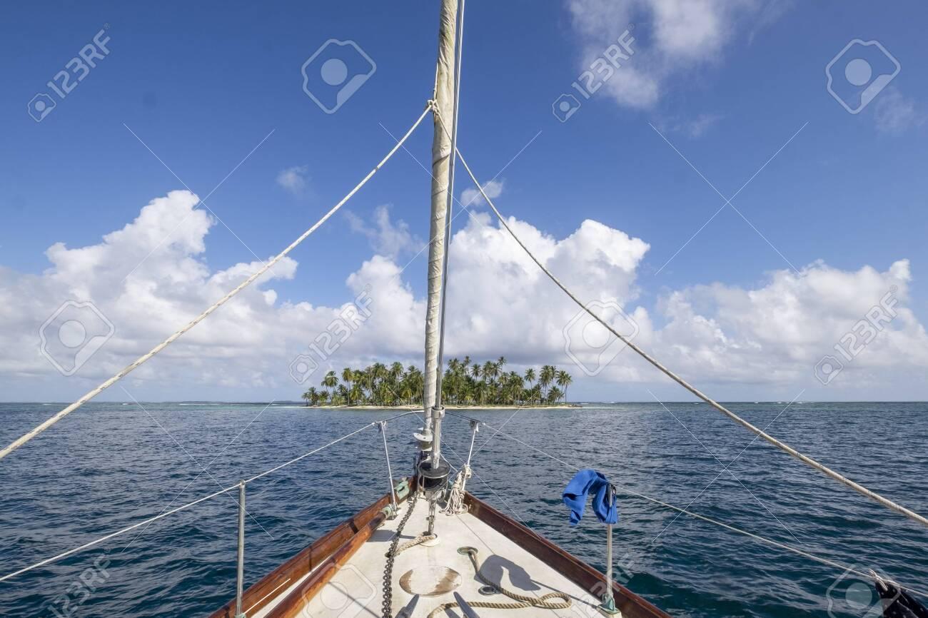 Sailboat prow point to palm tree island in San Blas archipelago - 135167503