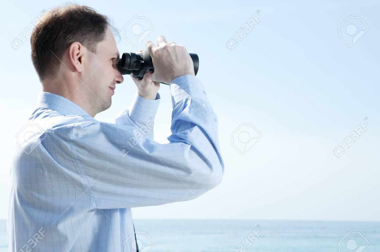 Businessman with binoculars against blue sky Stock Photo - 4901635