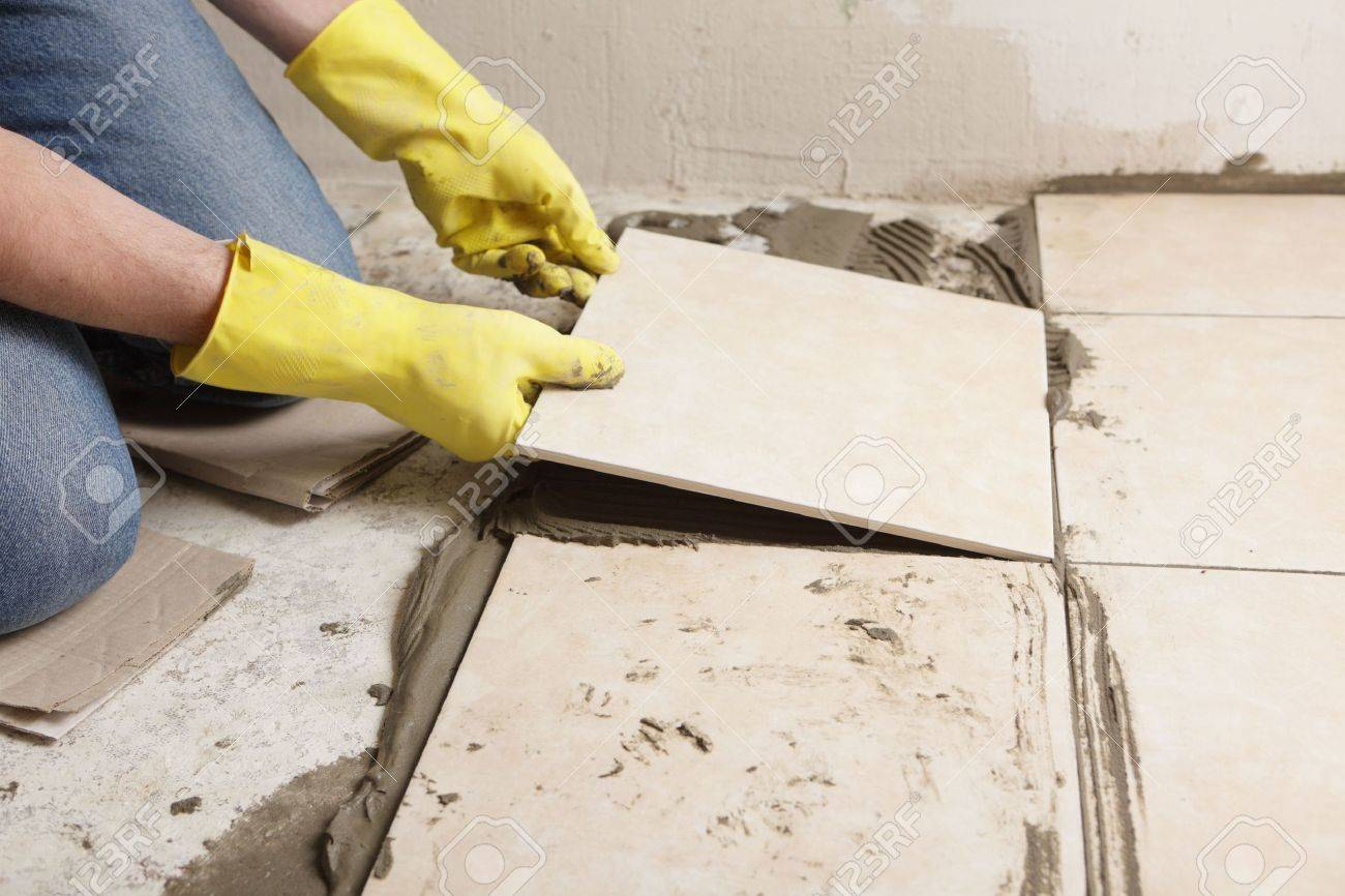 Tiler installing ceramic tiles on a floor stock photo picture and tiler installing ceramic tiles on a floor stock photo 6697379 dailygadgetfo Image collections