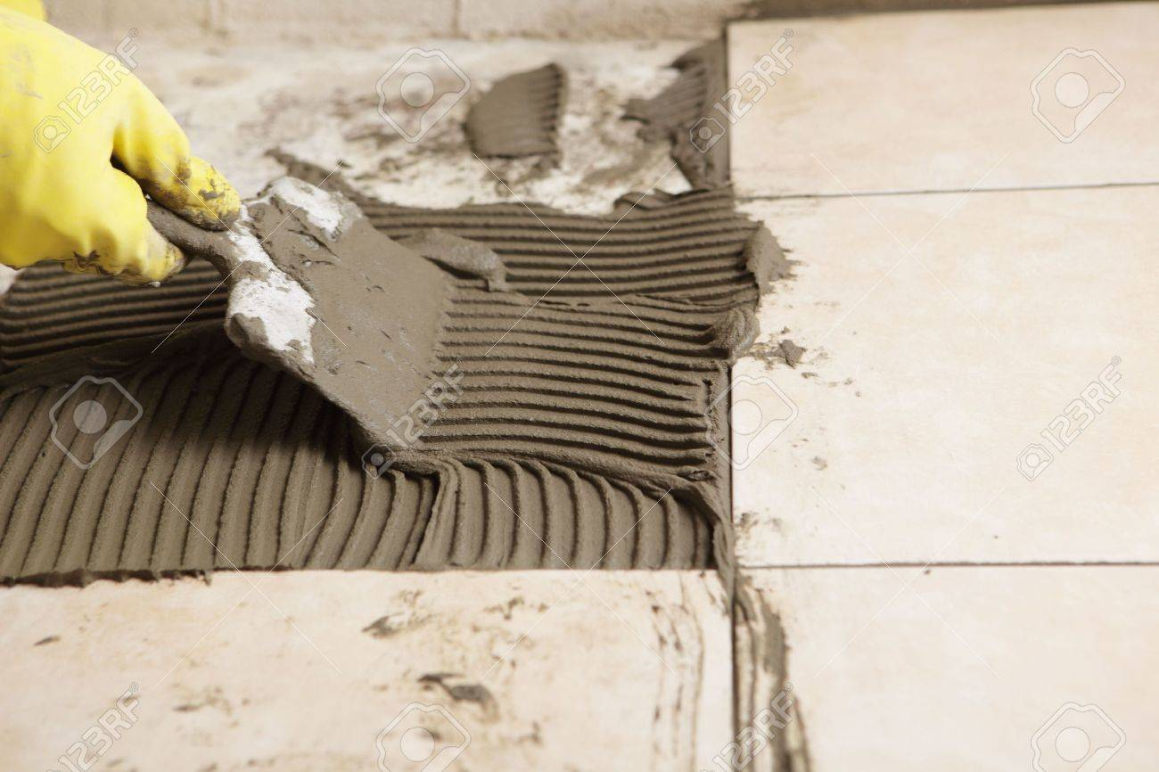 Tiler installing ceramic tiles on a floor Stock Photo - 6775750