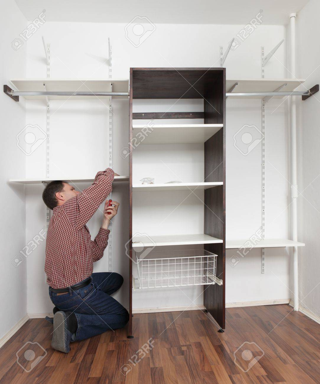 Man assembling the closet with wooden shelves Stock Photo - 9948804