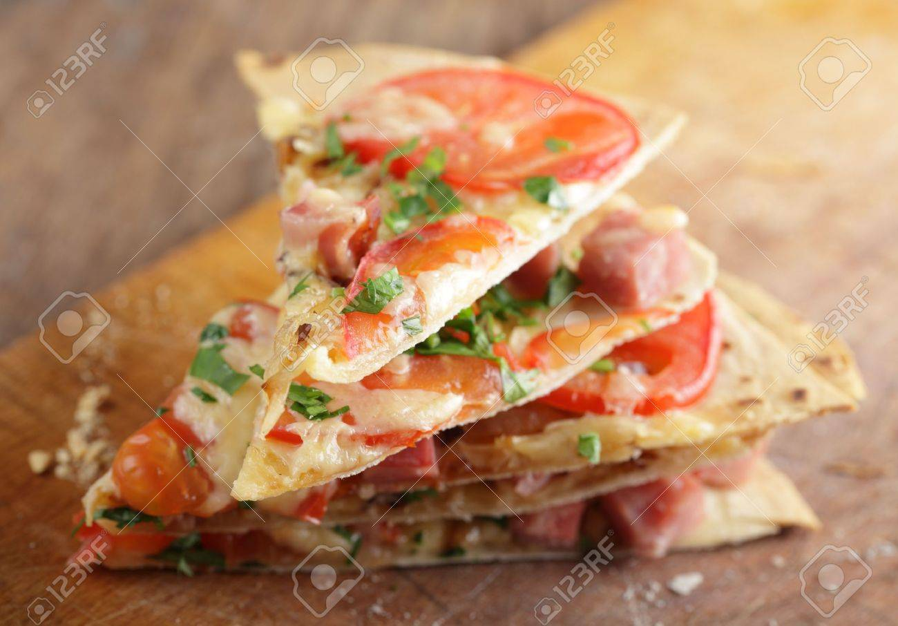 Stack of tortilla pizza slices on the wooden cutting board Stock Photo - 9820262