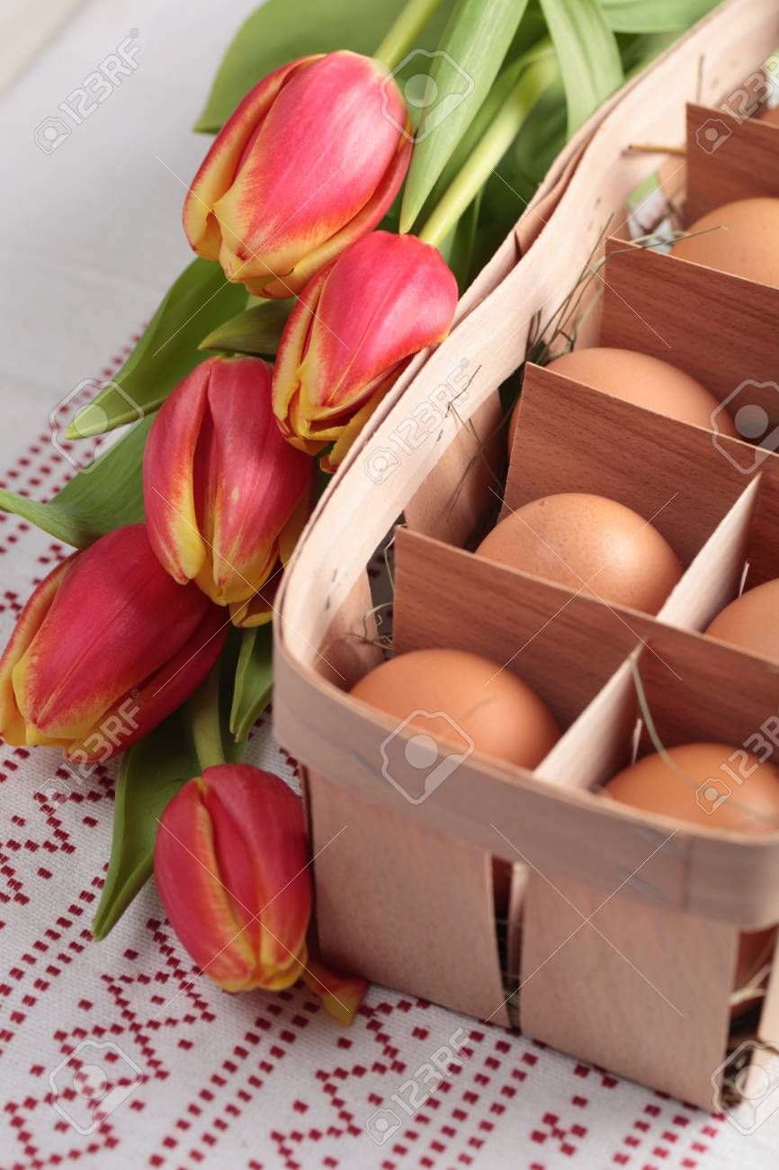 Eggs in a basket and a bunch of tulips Stock Photo - 12726678