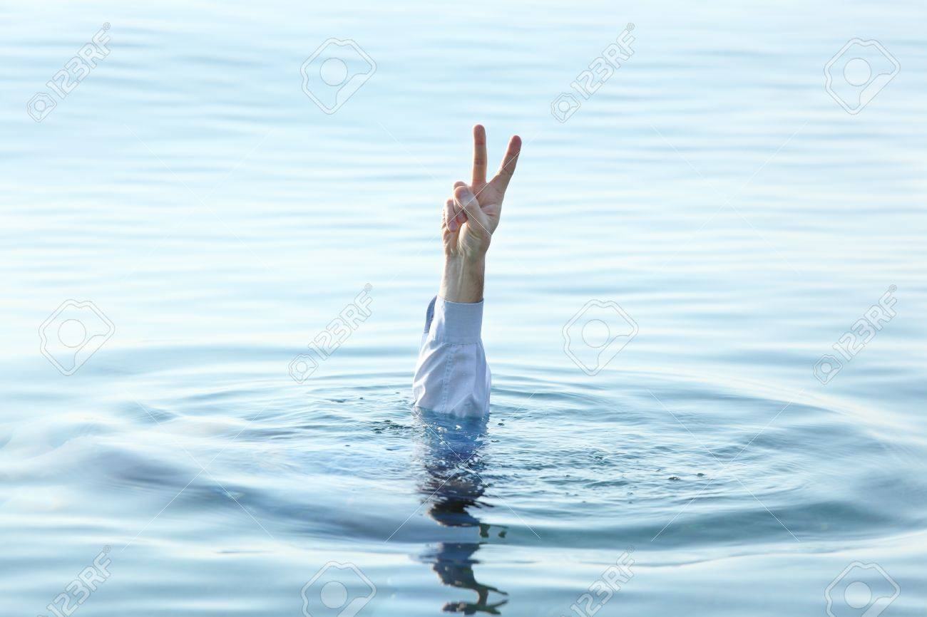 Sinking man showing victory sign stock photo 15729834