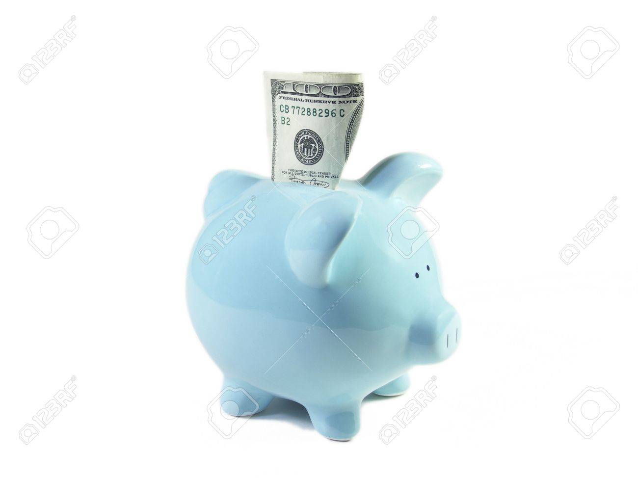 U.S. one hundred dollar bill stuck partially into a blue ceramic piggy bank. Isolated on white. Shallow depth of field. Focus on top of bill. Stock Photo - 263436