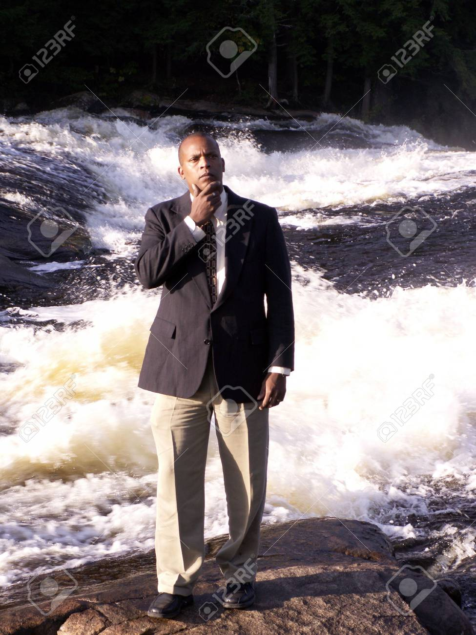 business man in a suit standing and thinking in front of a rushing river Stock Photo - 270537