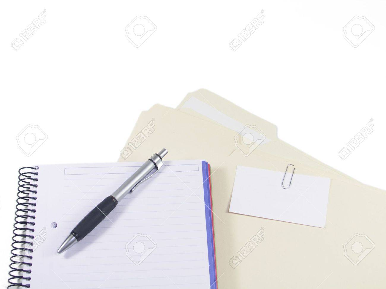 A Pen Blank Notebook And Folders With Business Card Paperclipped