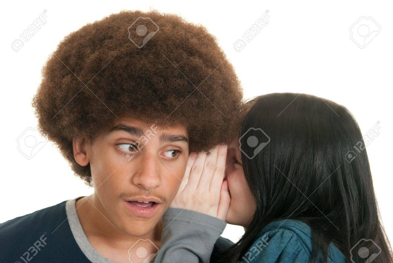 A young Caucasian girl whispers a secret to a mixed-race teen boy Stock Photo - 5819377