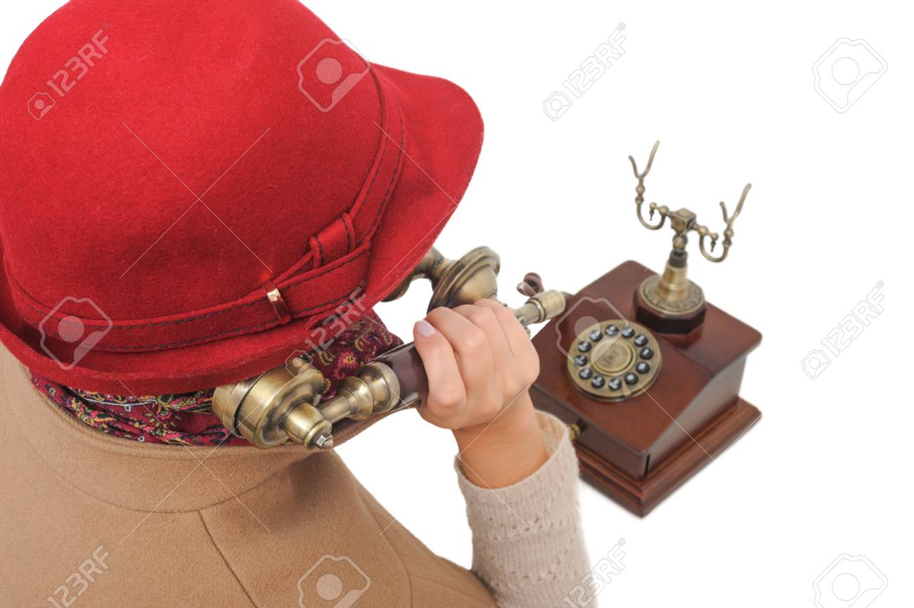 Old-fashioned woman in red hat is talking old-fashioned phone on white isolated background Stock Photo - 19927969