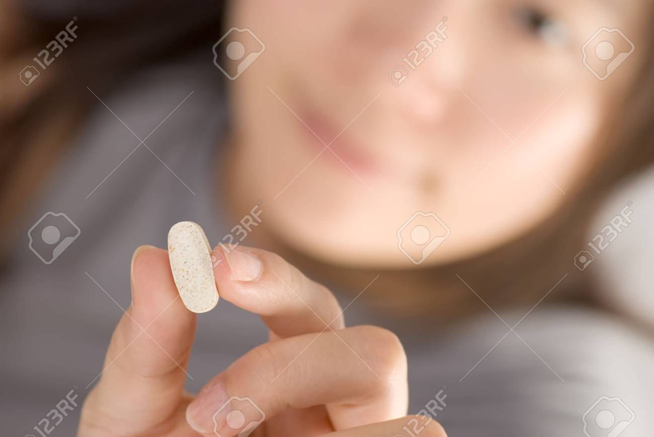 Medicine concept of woman holding one pill. Stock Photo - 6469192