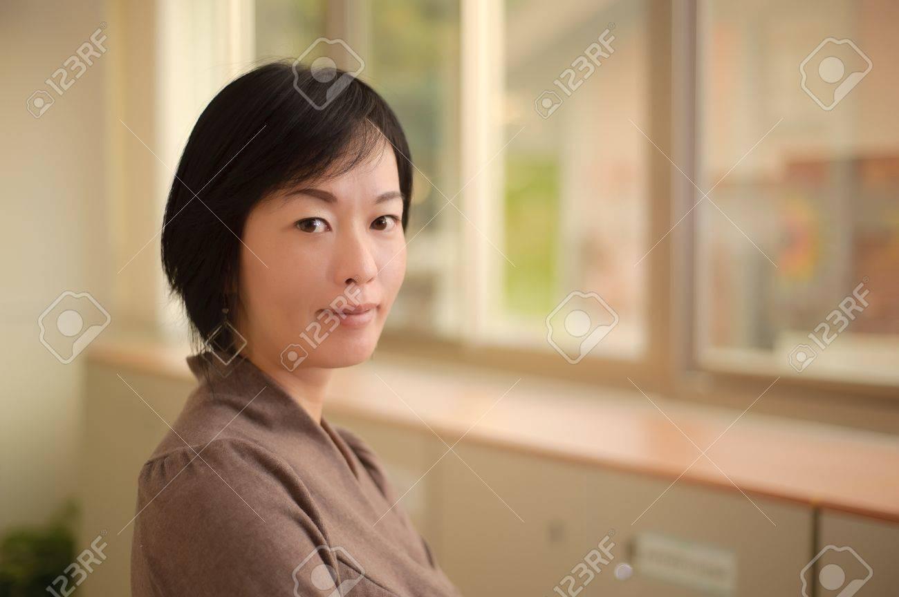 Kindly Asian woman face, closeup portrait indoor. Stock Photo - 8435322