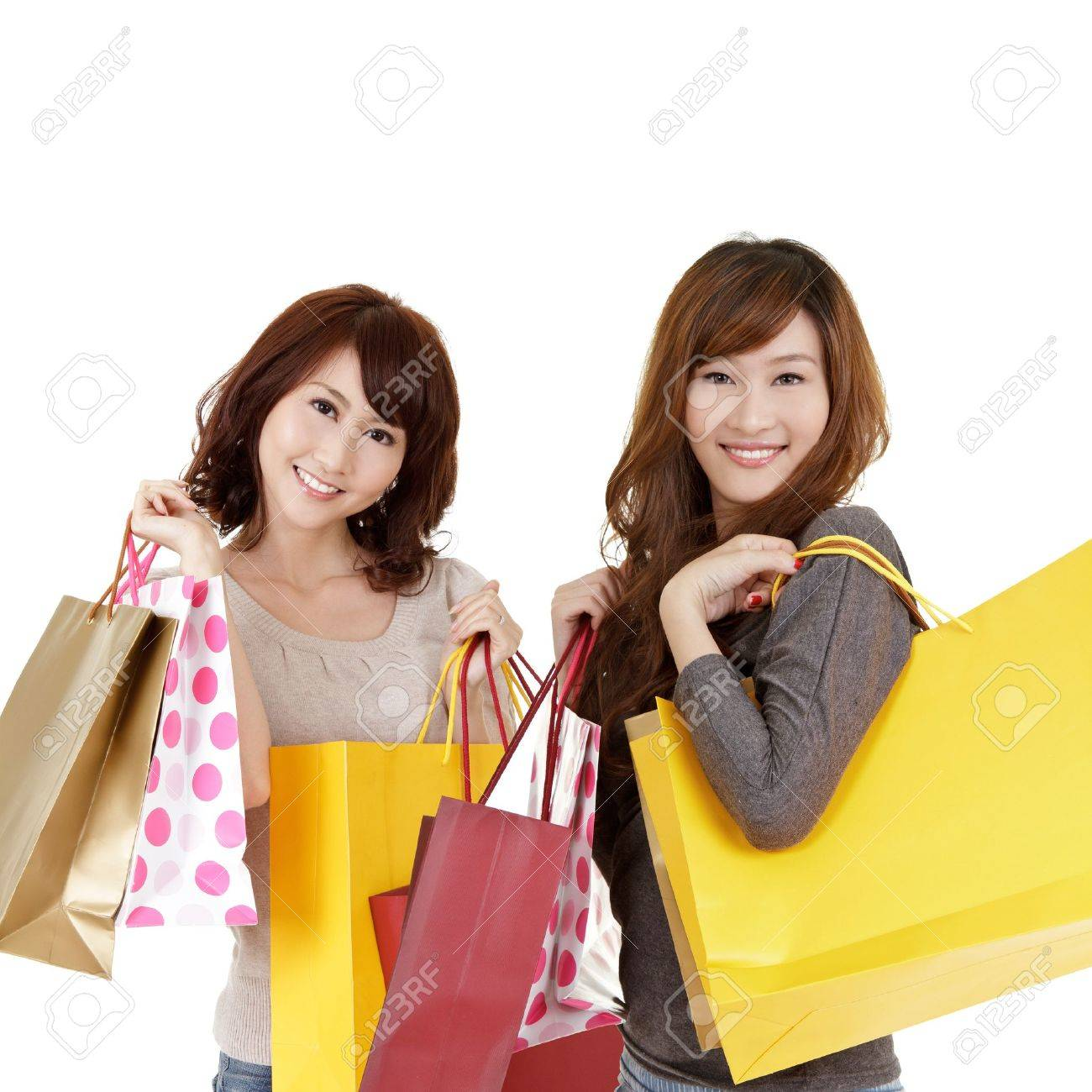 Shopping women, closeup portrait of two lady holding bags and smiling on white background. Stock Photo - 9113896