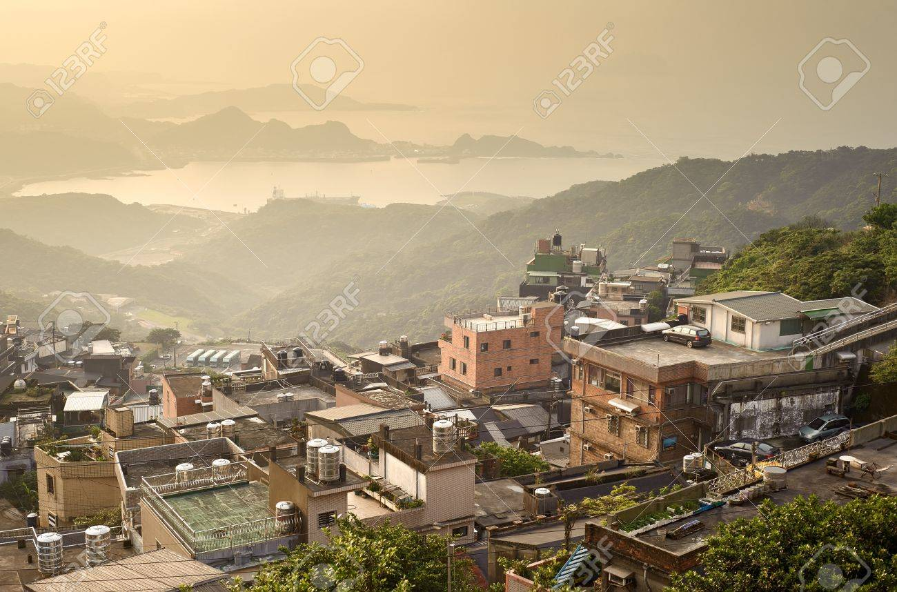 City sunset scenery with buildings on hill and harbor far away in Jiufen(Jioufen), Taiwan, Asia. Stock Photo - 9375418