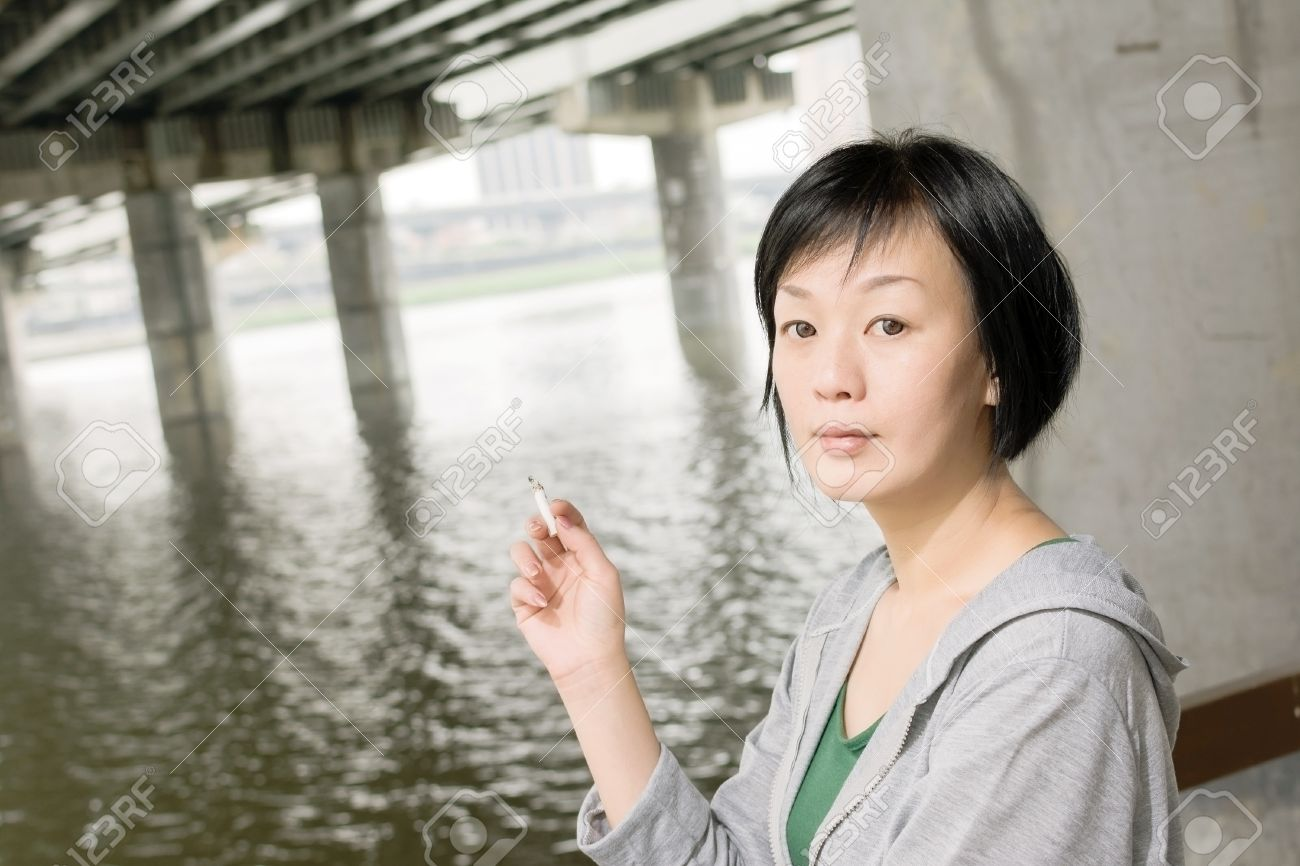 closeup portrait of mature asian woman smoking under bridge at