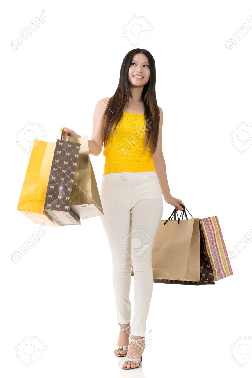 Attractive Asian Woman Holding Shopping Bags And Walking In Studio ...