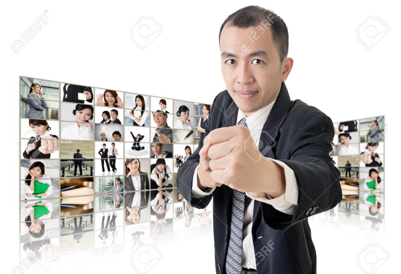 Asian business man or boss standing in front of TV screen wall showing pictures of business concept. Stock Photo - 26654702