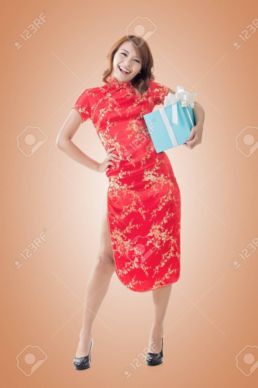 538079103f5f 35375496-sorridente-vestito-donna-cinese -cheongsam-tradizionale-in-piedi-e-in-possesso-di-un-regalo-a-capodan.jpg