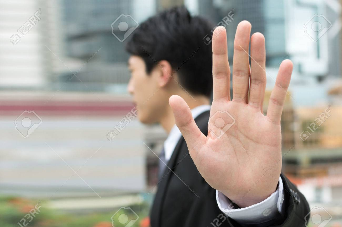 Stop gesture, side view of Asian businessman standing in the city. - 49684140