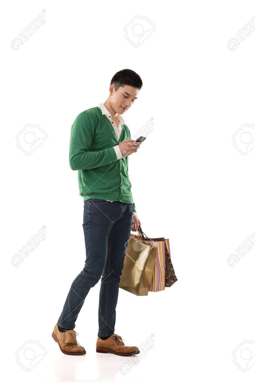 Asian young man holding shopping bags and using cellphone, full length portrait isolated. - 52821579