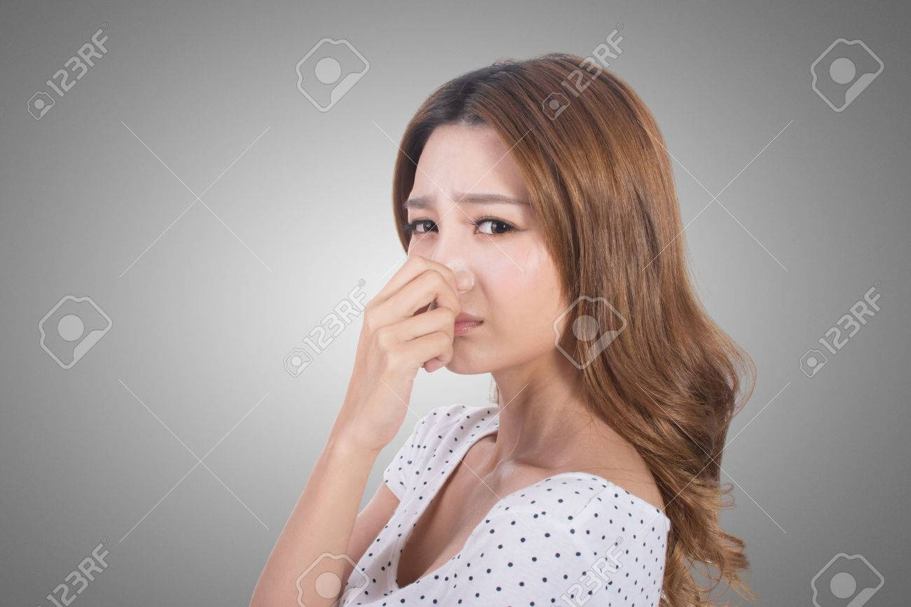 Portrait of a young woman holding her nose because of a bad smell. - 52915603