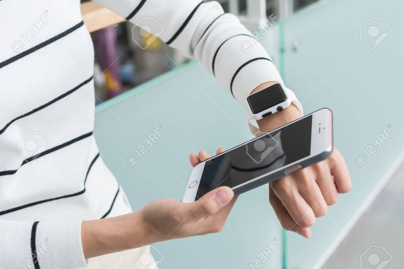 Young Woman using wearable watch connecting to mobile phone - 60015463