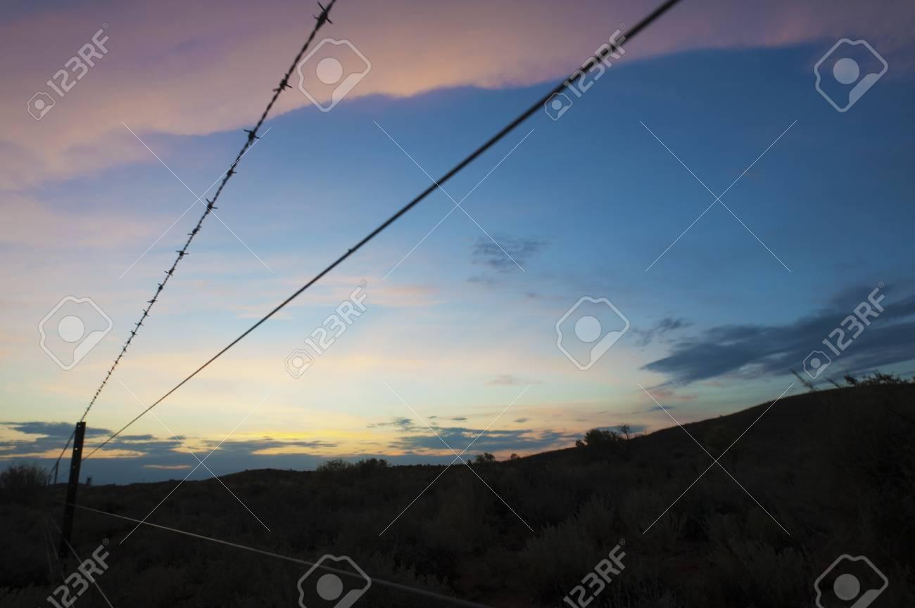 blick entlang eines bauern zaun als der sonnenuntergang die wolken
