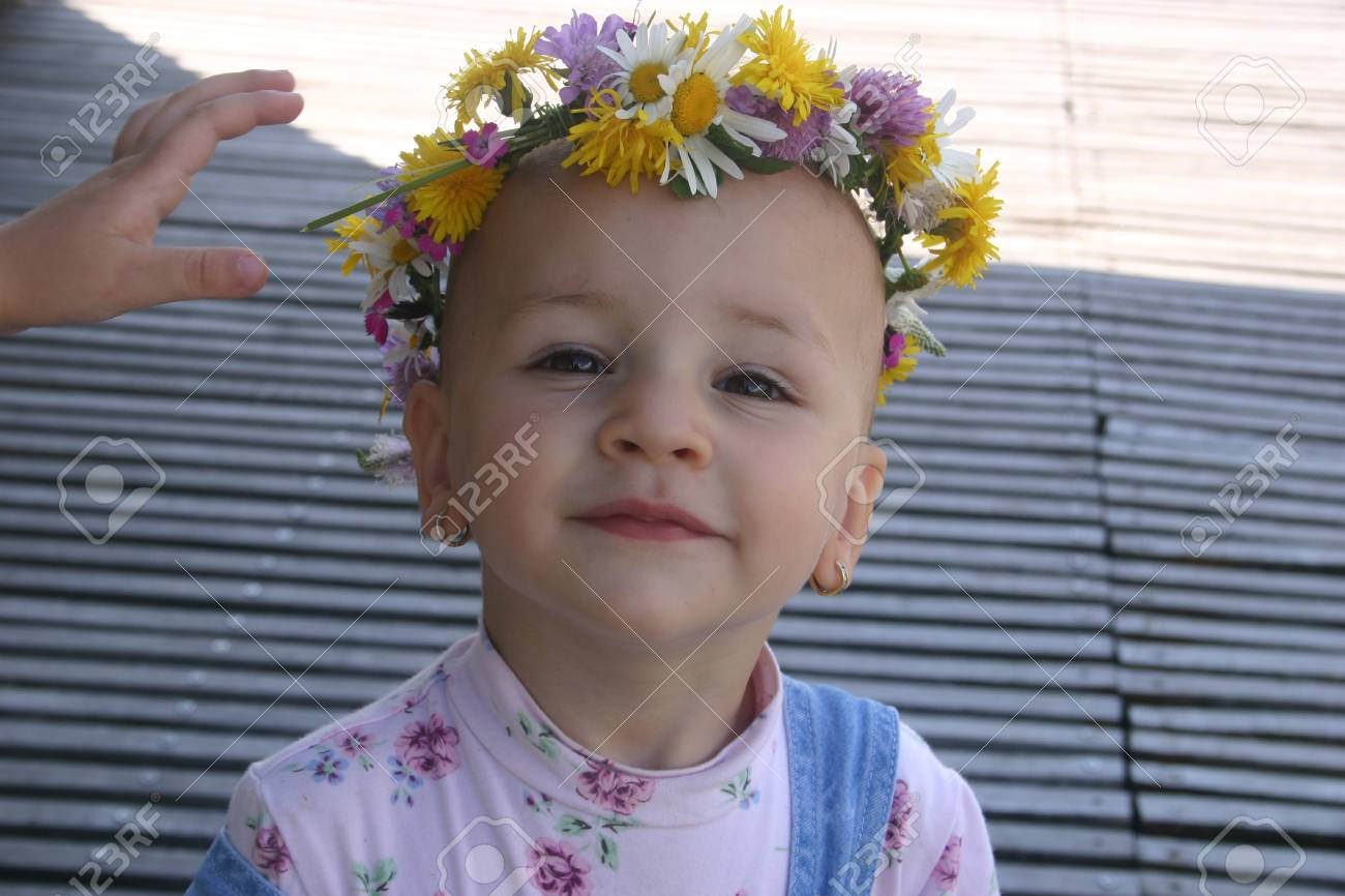 Portrait Of Little Girl Wearing A Natural Flower Crown Stock Photo